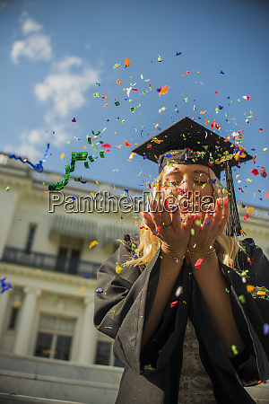 graduating student blowing confetti off her