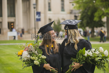 graduating students carrying bouquet at campus