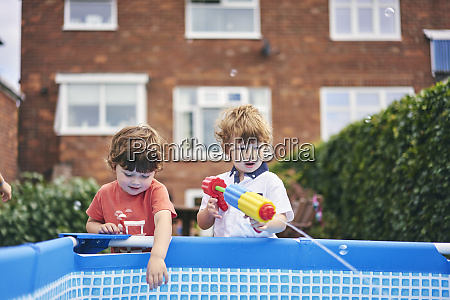 boys playing with water gun by