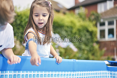 girl pointing into pool