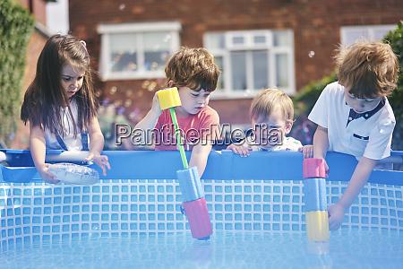 children filling up water gun by