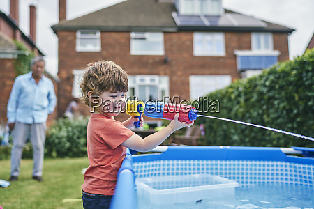 boy playing with water gun by