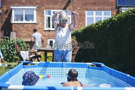 grandmother watching grandchildren playing in pool