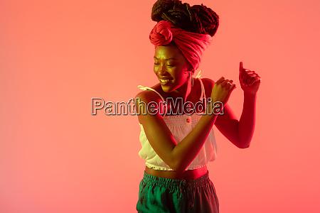 woman with headscarf dancing against peach