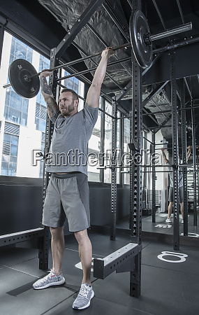 man performing overhead press with barbells
