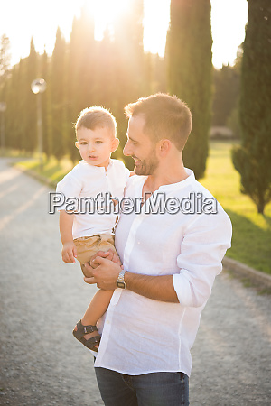 father carrying son in park