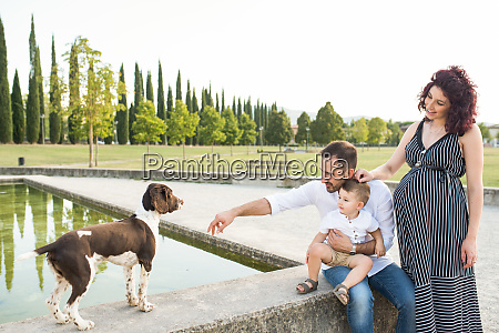 parents with son playing with dog