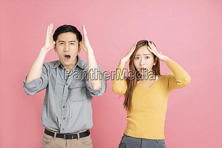 young couple afraid and shocked with