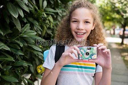 girl holding film camera