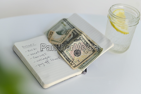 budget list in notebook with money