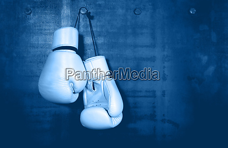 white leather boxing gloves hanging on