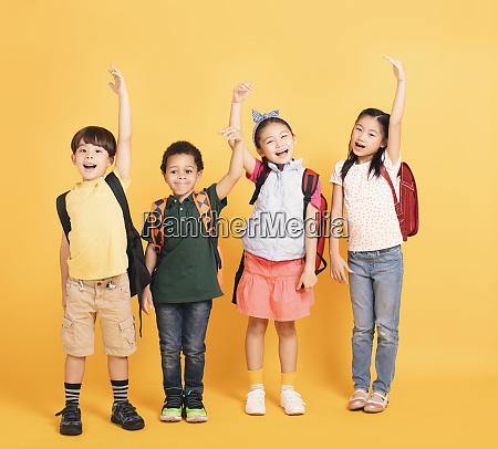 happy school children raised hands together