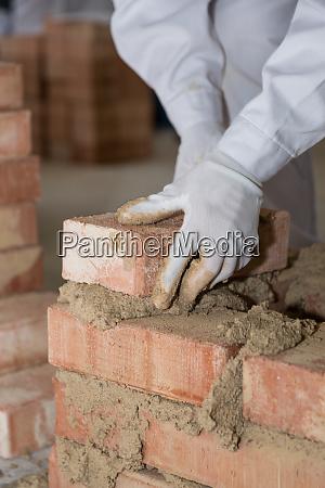 mason builds brick wall close