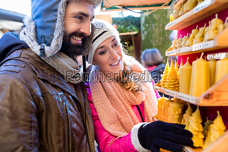 couple on christmas market buying candles