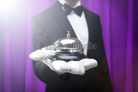 male waiter holding service bell on