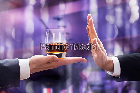 hand rejecting glass of whiskey offered