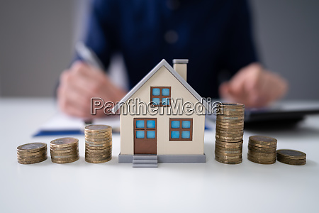 businessman calculating tax by model house