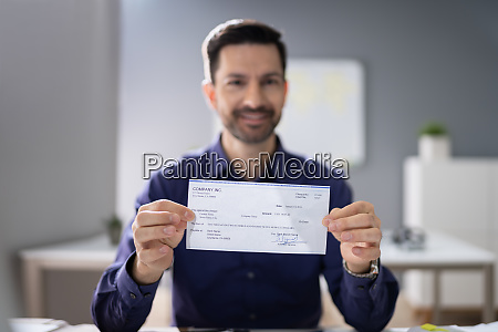 smiling businessman holding cheque