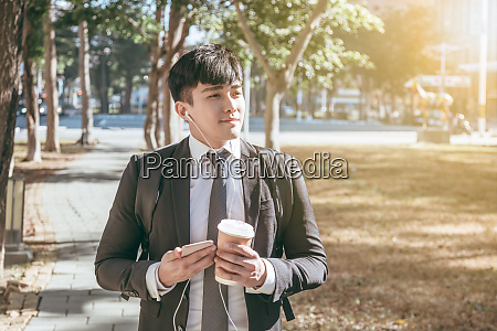 businessman holding mobile phone while walking