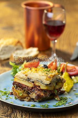 portion of greek moussaka on wood