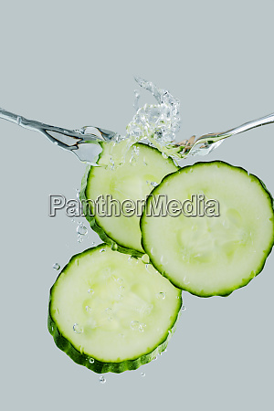 three cucumber slices falling into the