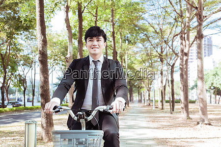 businessman riding bicycle to work on