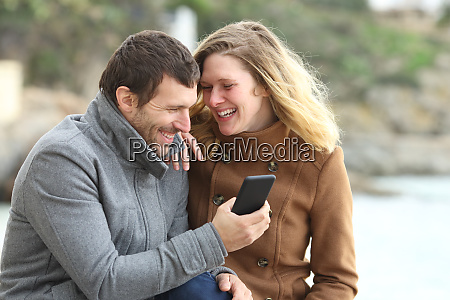 happy couple laughing talking about phone