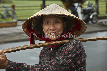 vietnamese woman carrying produce on a