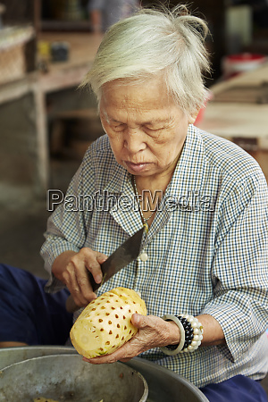 elderly woman cutting pineapple can duoc