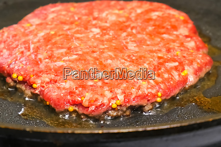 raw cutlet is fried in pan