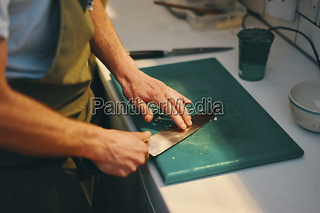 chef holding knife on chopping board