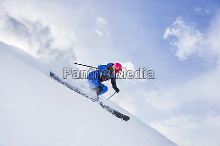 skier skiing and spraying snow kuehtai