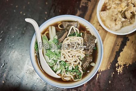 bowl of beef noodles on wooden