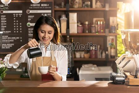 female barista making coffee