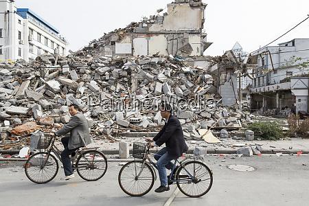 china shanghai men ride bicycles past