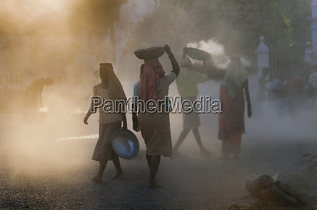 sunlit dust around laborers goa india
