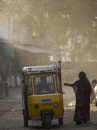 woman paying fare to rickshaw driver