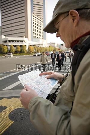 japan tokyo male tourist reading map