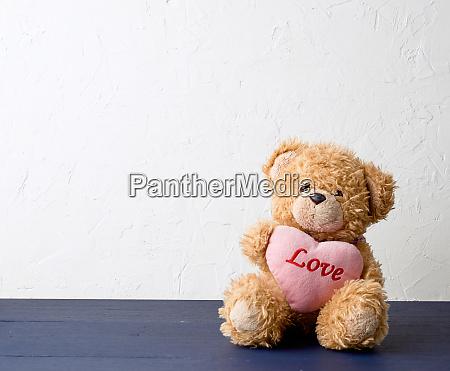 cute brown teddy bear holding a