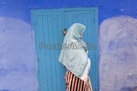 woman in narrow lane chefchaouen morocco