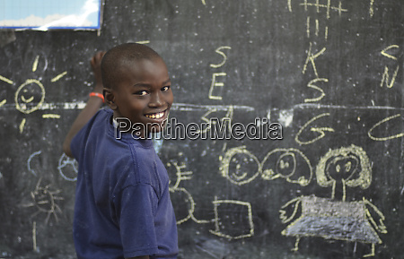 kenya nairobi little boy writing with