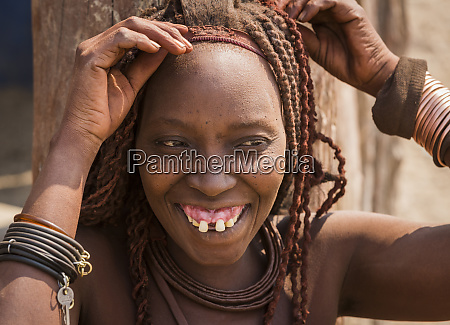 africa namibia opuwo himba woman fixing