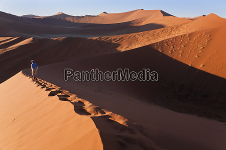 middle aged man climbing sand dunes