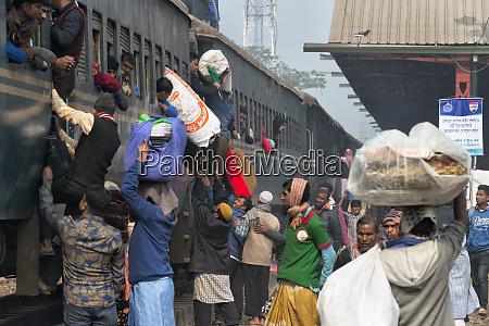 people climbing onto a crowded train