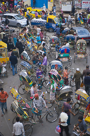 rickshaws in traffic on a street