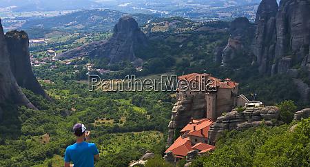 tourist watching monastery of roussanou meteora