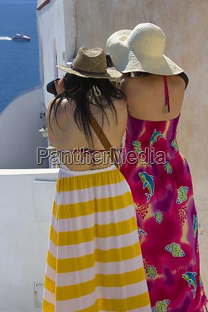 tourists photographing the aegean sea oia