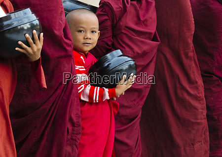 novice monks holding alms wok waiting
