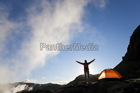 woman standing by tent at sunrise