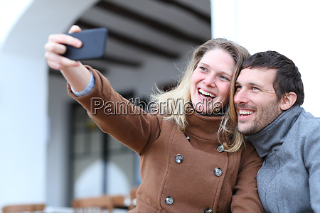 happy couple of adults taking selfies